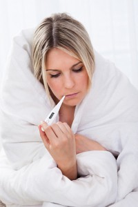 Ill woman with thermometer In mouth